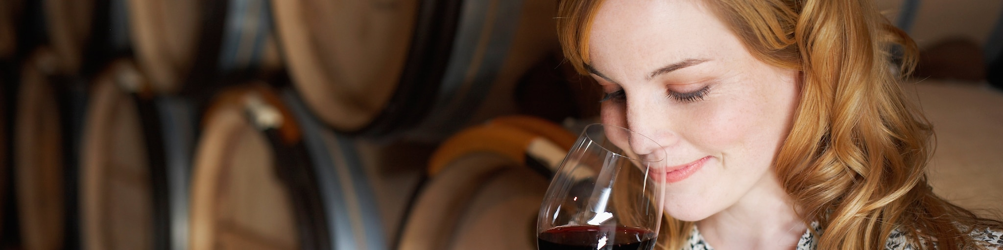 A woman sniffs the red wine in her wine glass