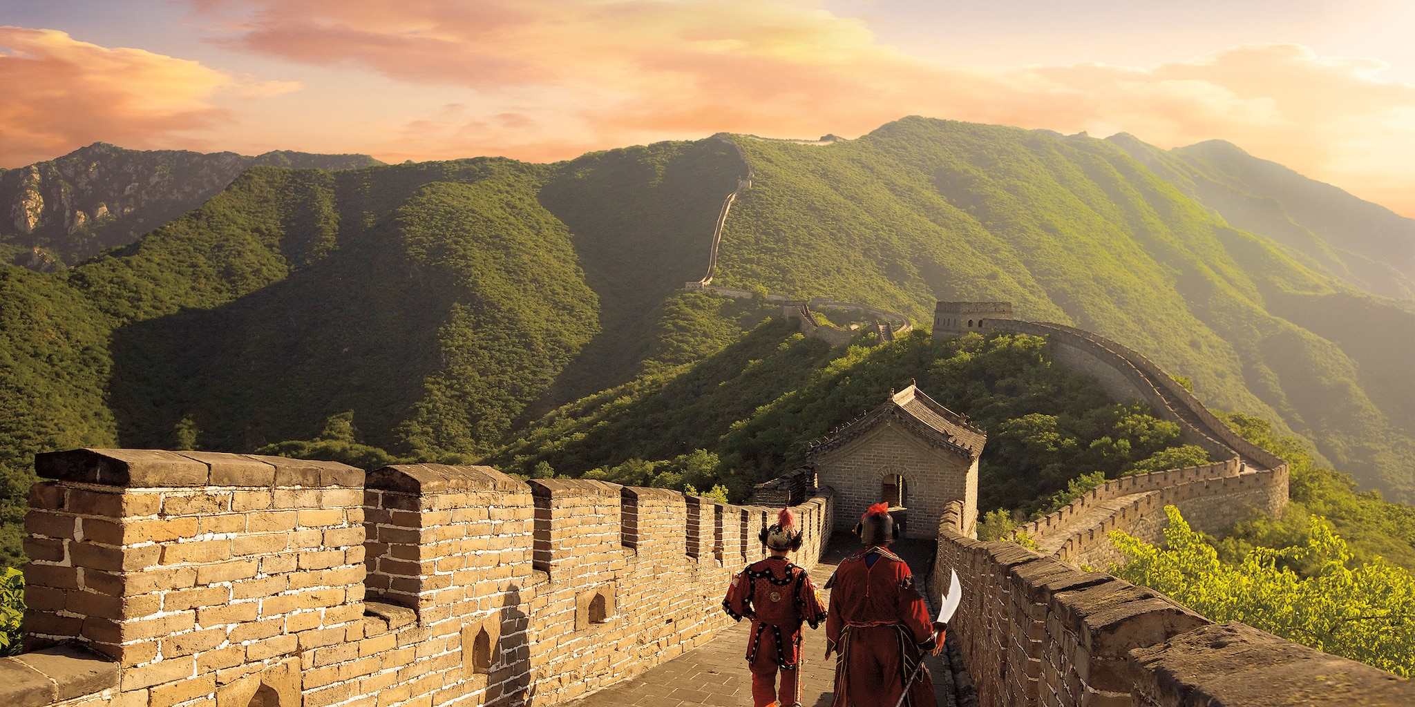 2 men walking dressed in centuries' old costumes walk along the Great Wall of China