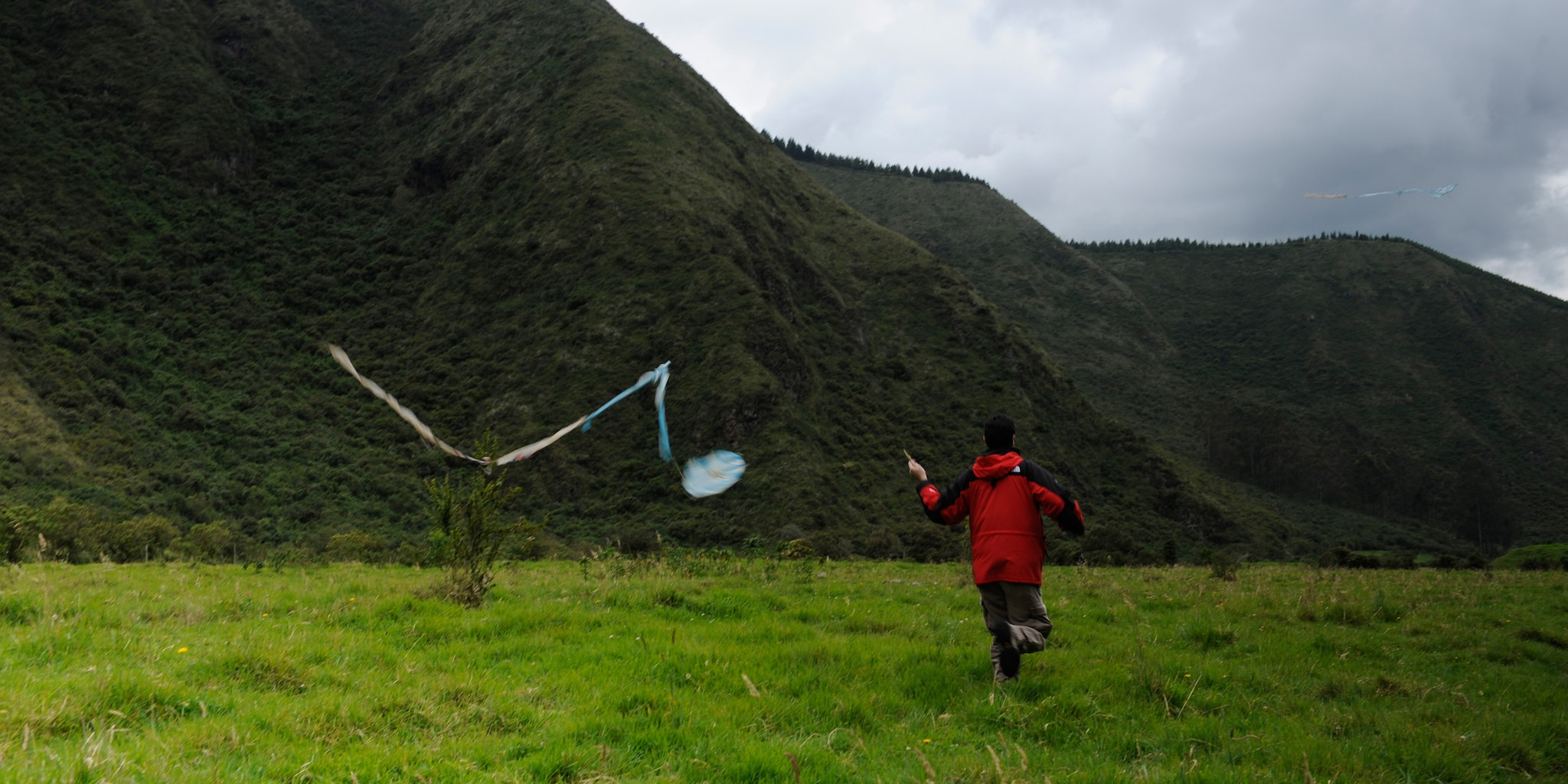 A boy flies his kite on a grassy plain at the foot of a hillside