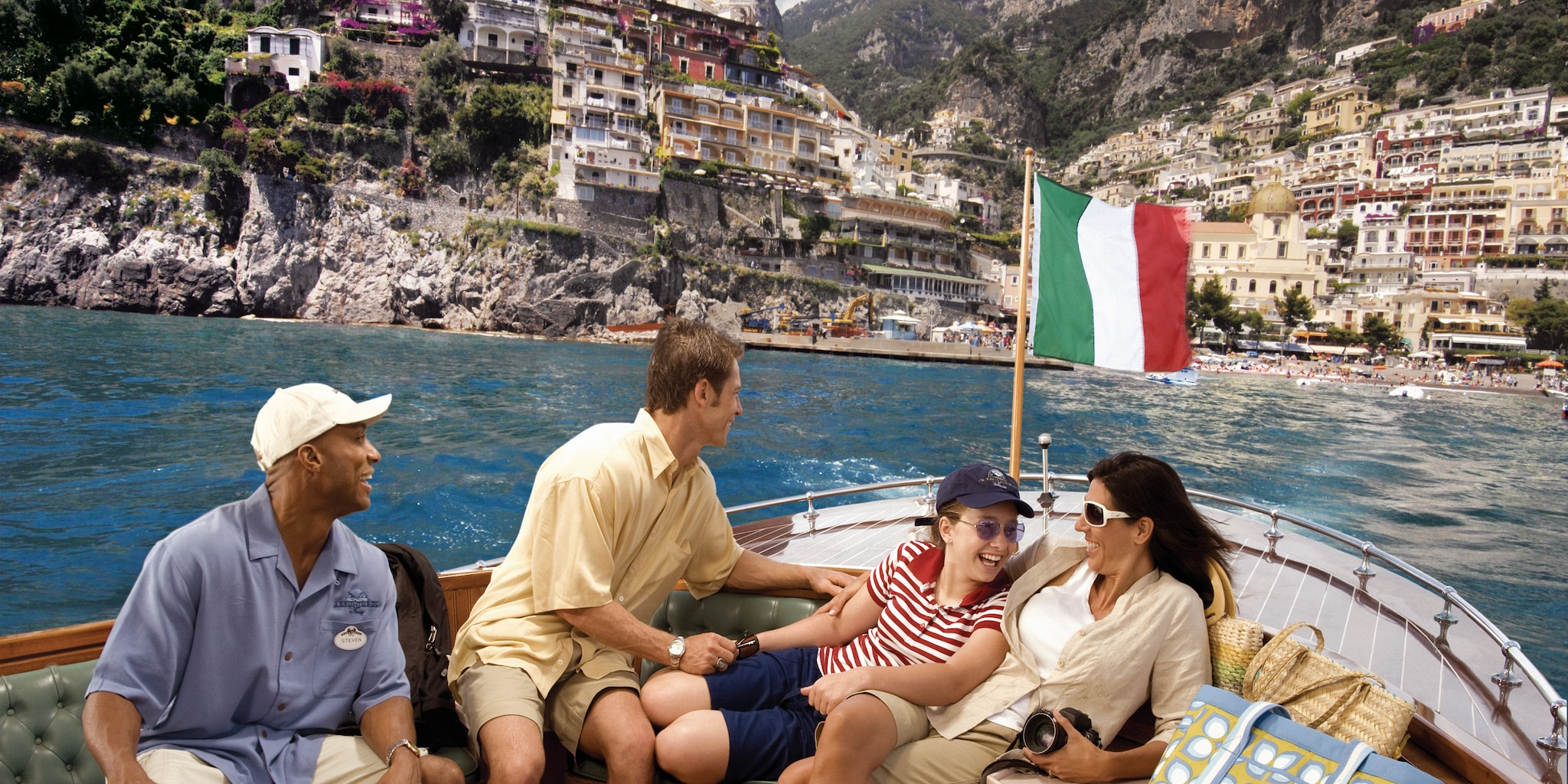 A family and an Adventure Guide sit on a boat cruising the scenic Amalfi Coast