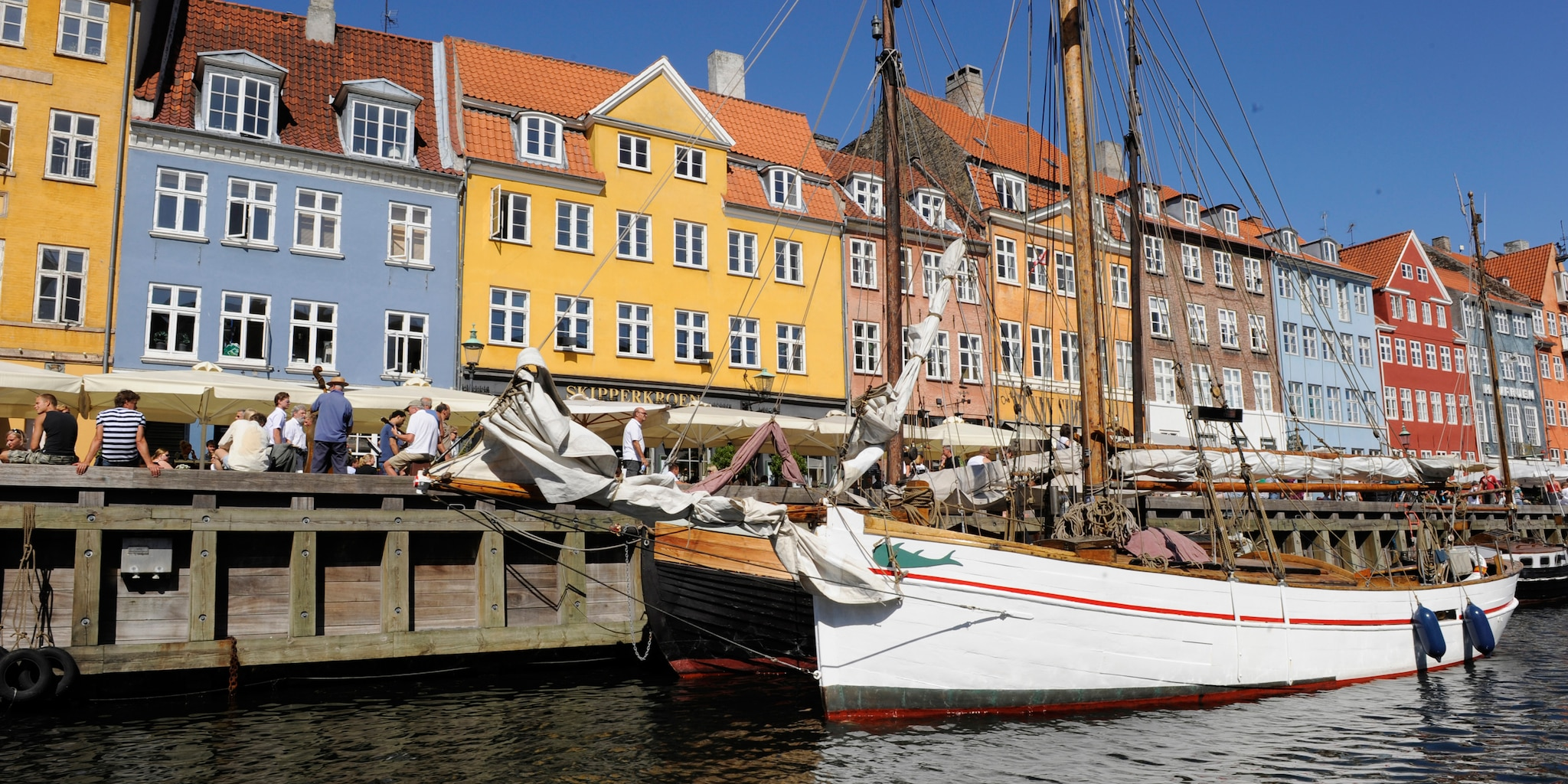 A boat docked at the Copenhagen harbor near European row houses