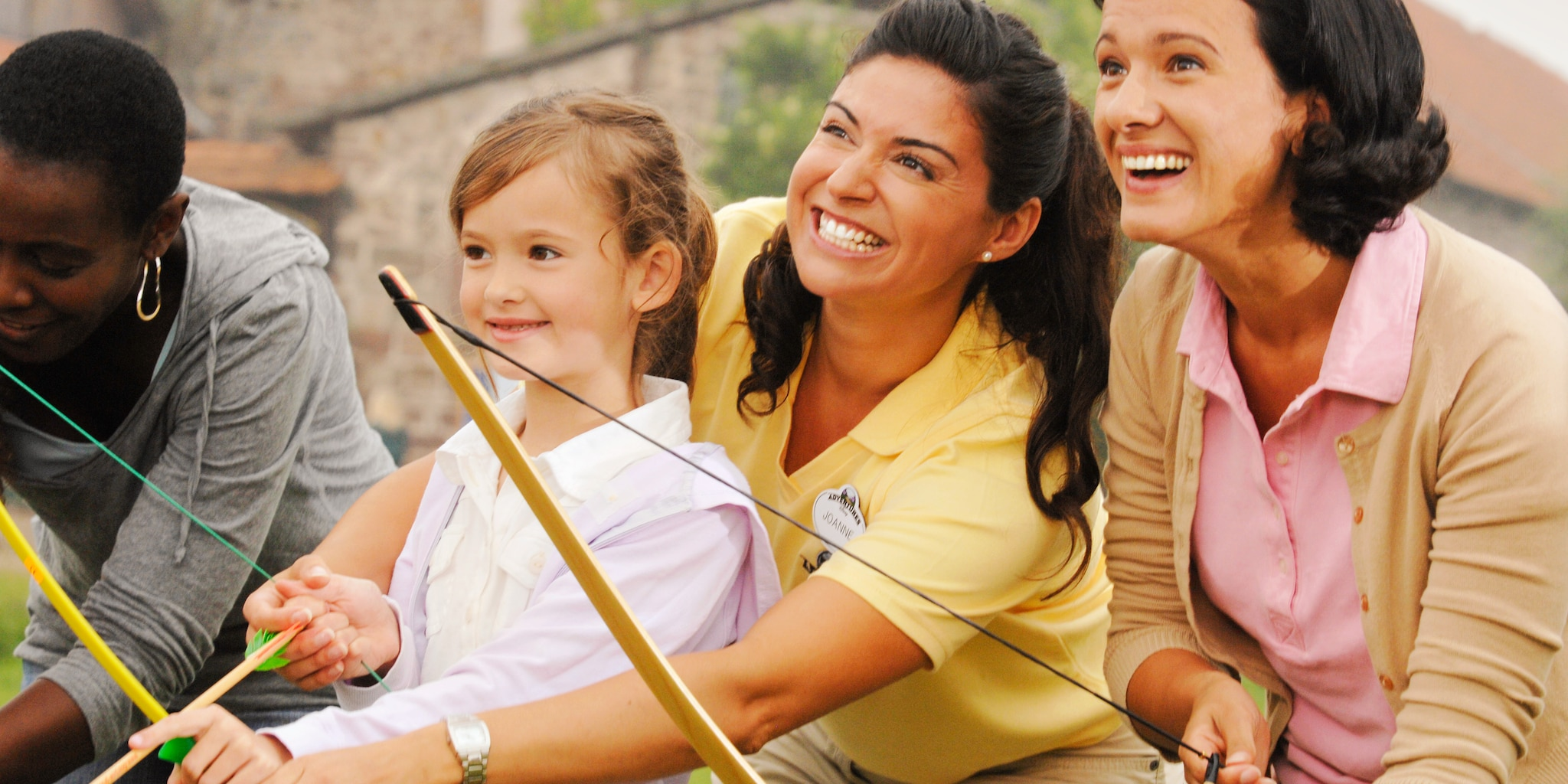 A female Adventure Guide shows a girl how to use a bow and arrow as her mother watches