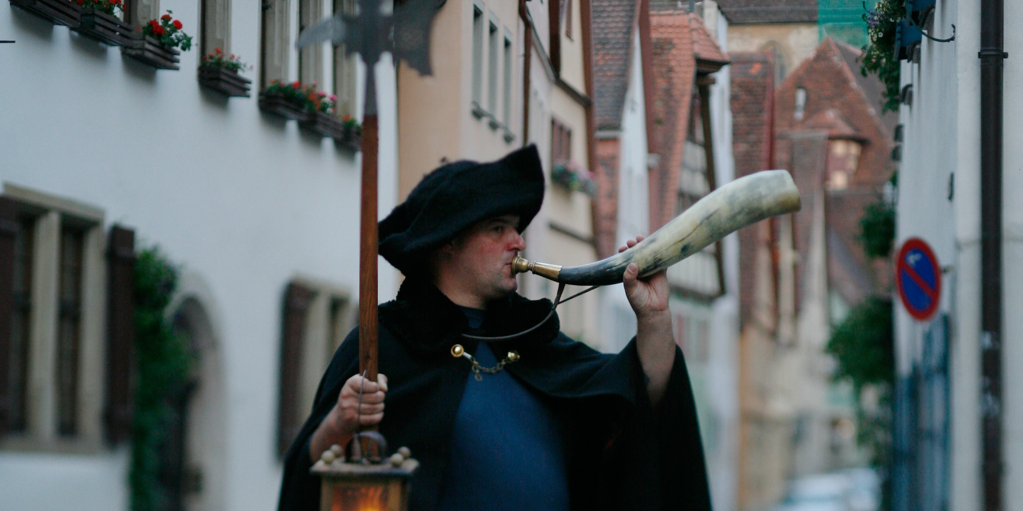 A night watchman wearing a three cornered hat and a cloak carries a lantern and blows a carved horn