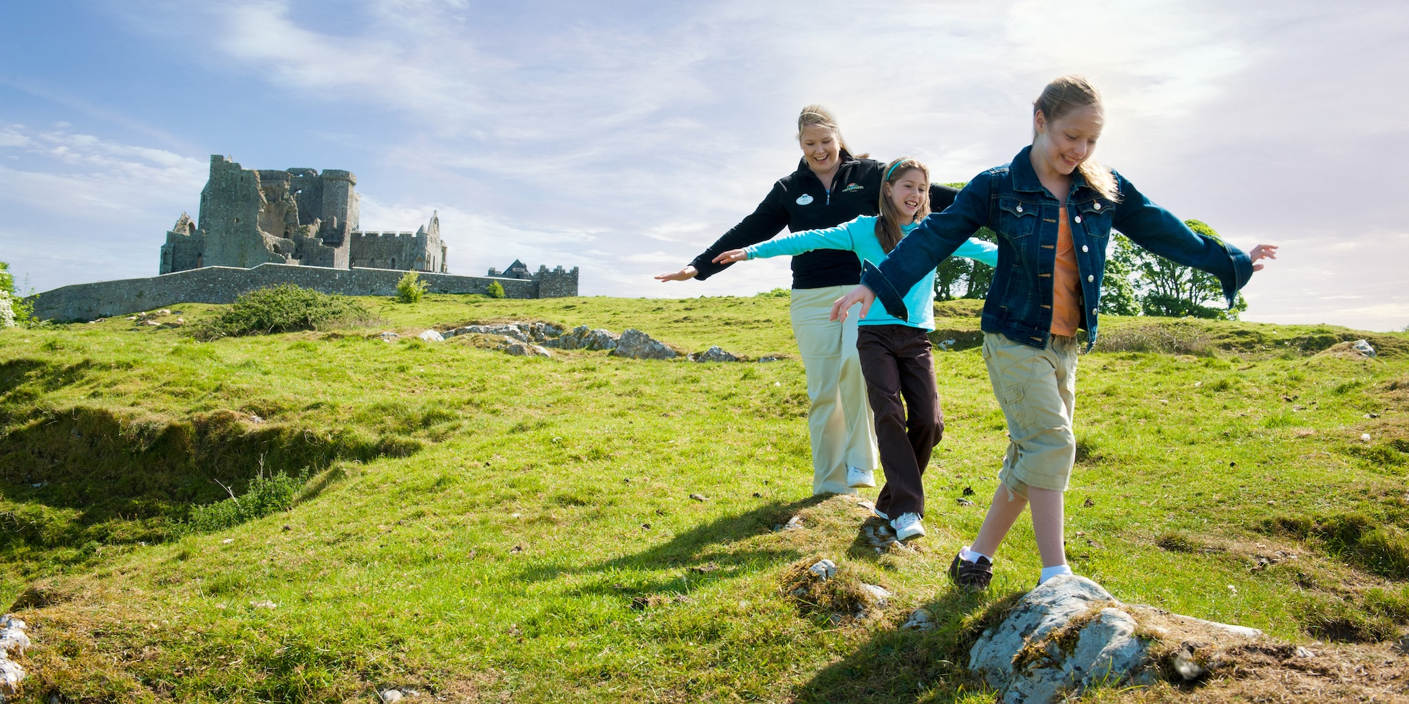 A female Adventure Guide and 2 girls walk on grass near the Rock of Cashel