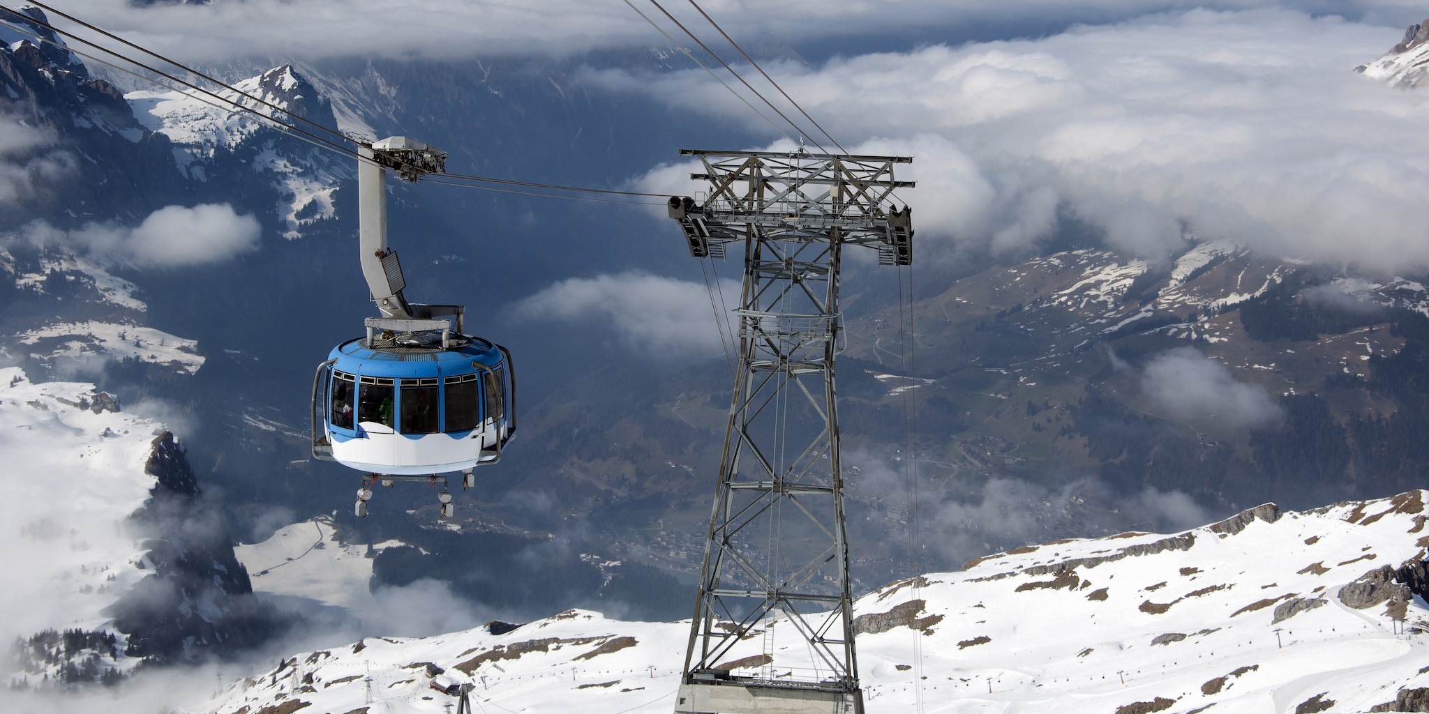 A an aerial cable car rides through a region with snow-covered mountains