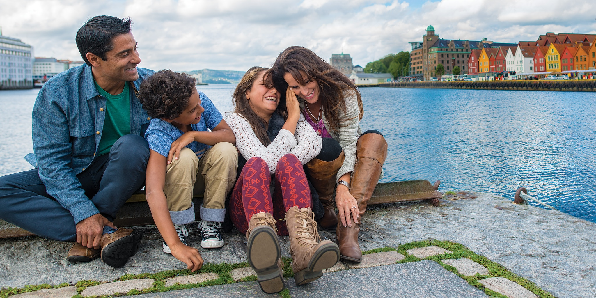 A family of 4 sits by the edge of a stone pier, overlooking the water next to the town of Bergen