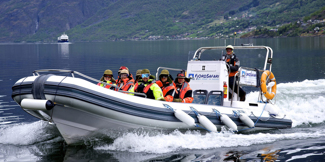 Passengers aboard a Fjord Safari power boat make waves as they cruise through the water