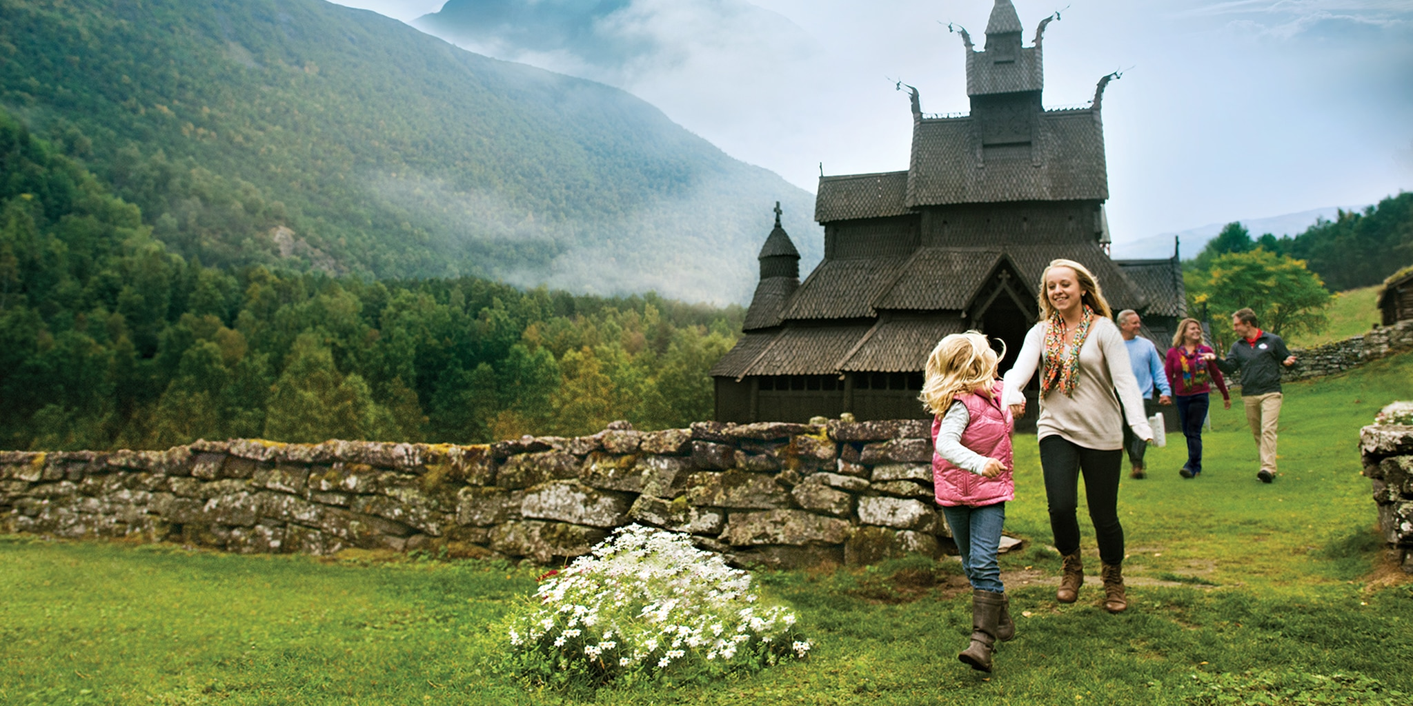 Two girls run ahead of their family, passing a stone fence in front of the Borgund Stave Church