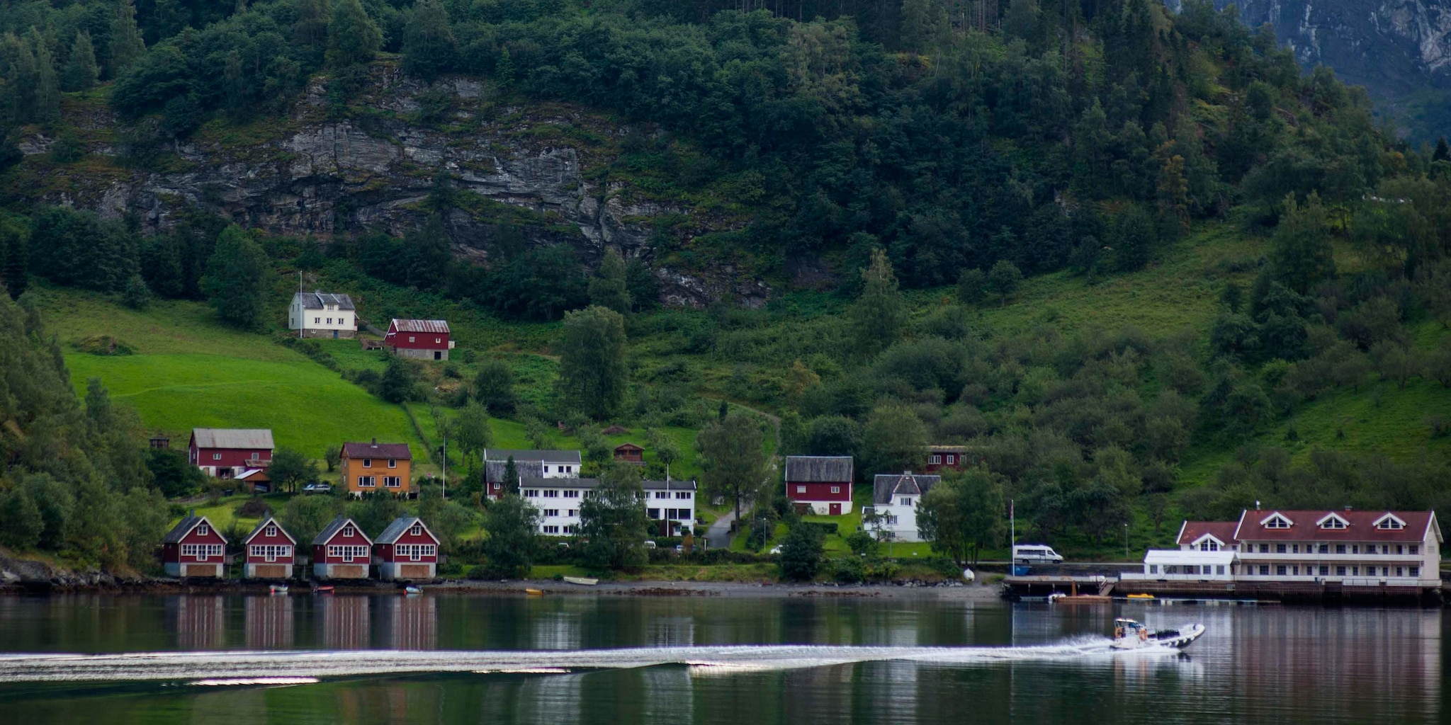 A boat passes a lakeside village that climbs into the nearby hills