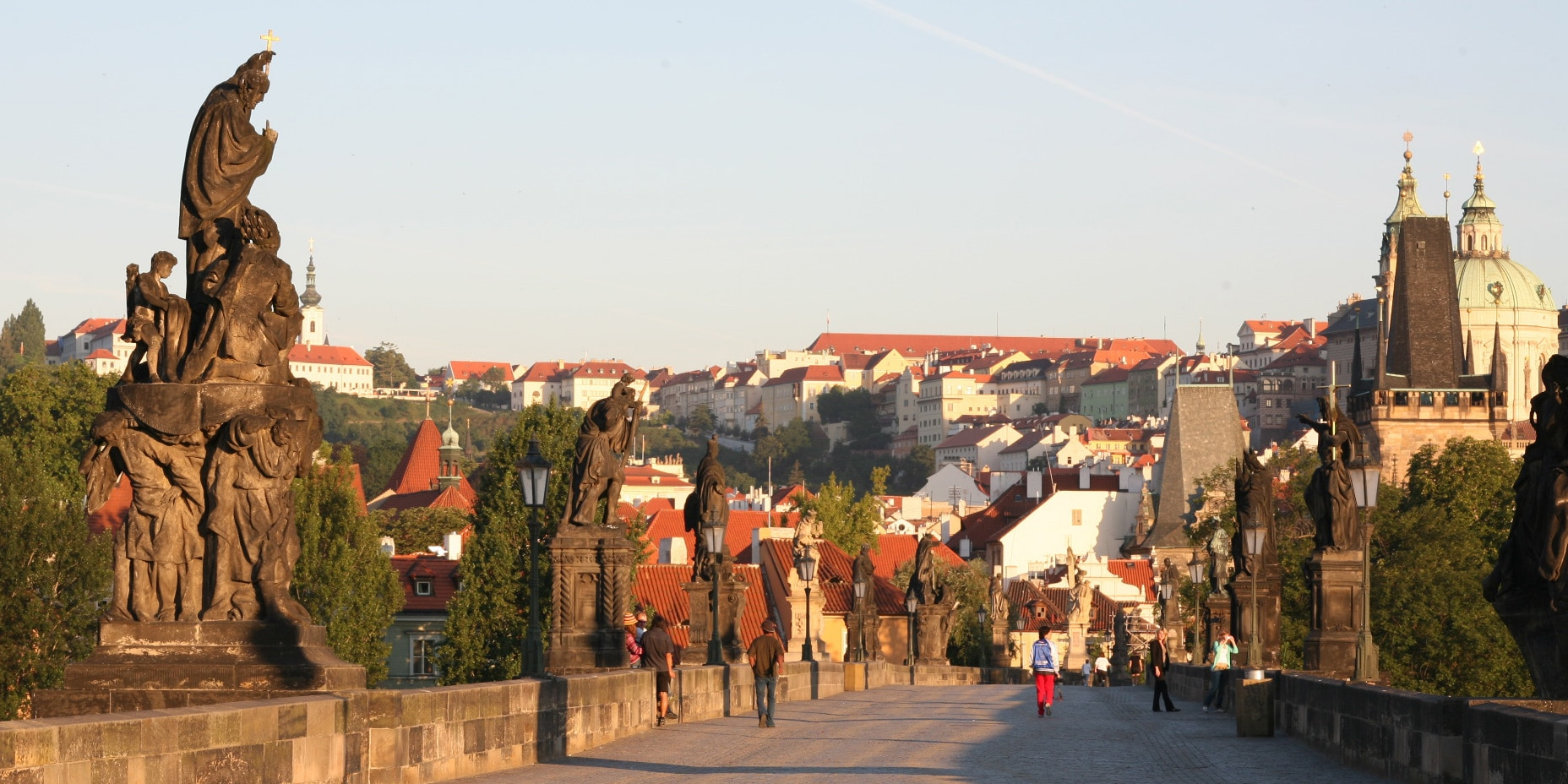 Statues featuring imposing figures line the stone walls on both sides of the Charles Bridge