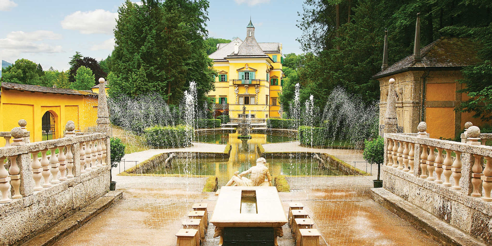 The fountains of Hellbrunn Palace spray water in symetrical lines in front of a statue