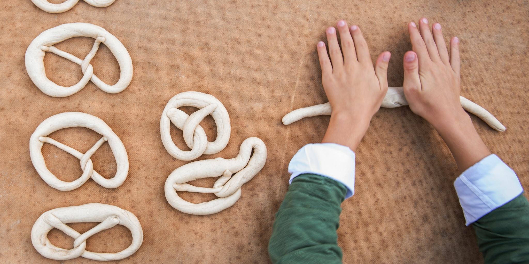 A pair of hands with rolled sleeves rolls out dough next to a few dough pieces twisted into pretzels