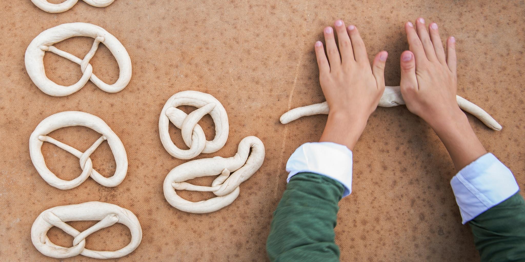 Hands roll dough into pretzels