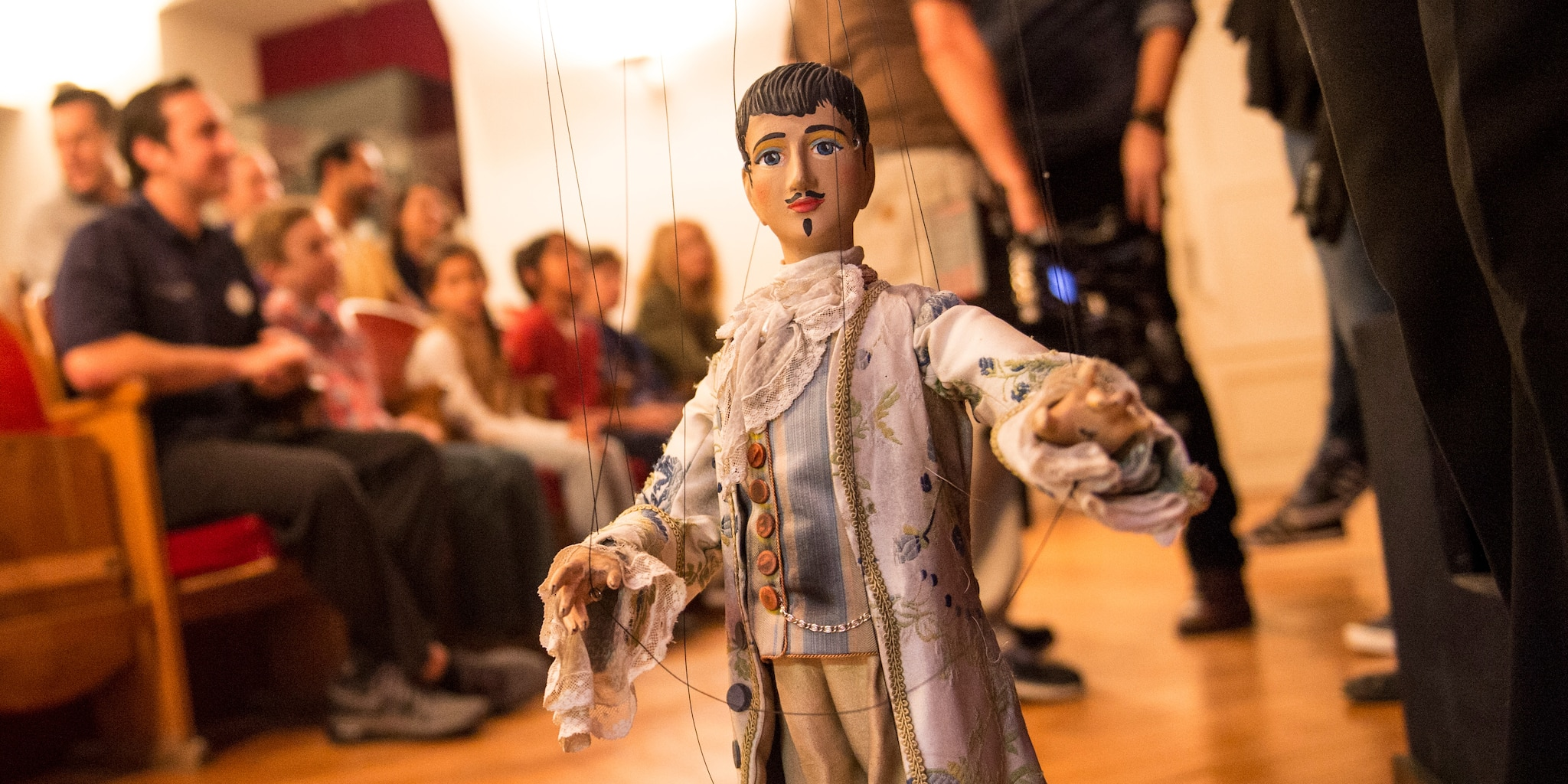 A handmade marioette with strings wears renaissance attire and sports a painted moustache