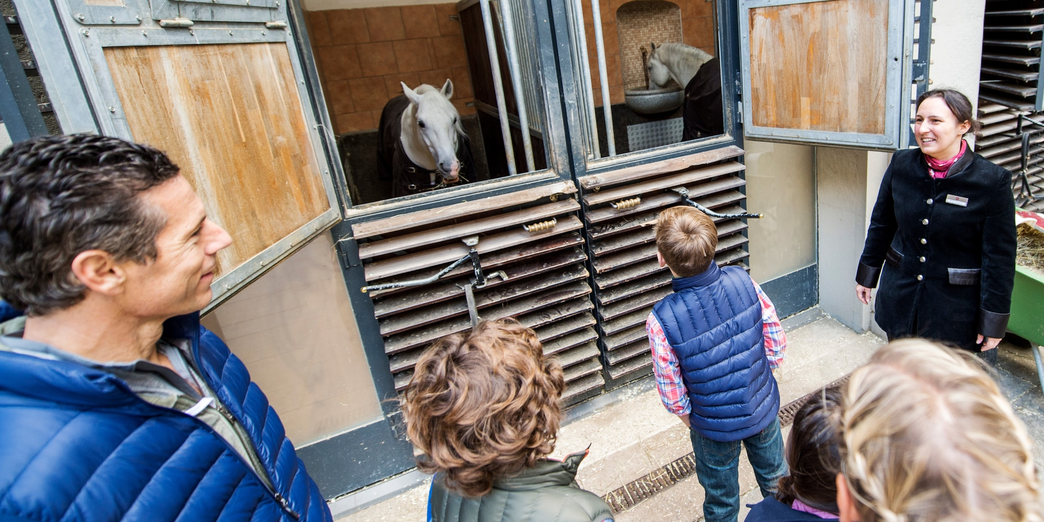 A family looks through an open stable door to see a pair of horses, one of whom is eating