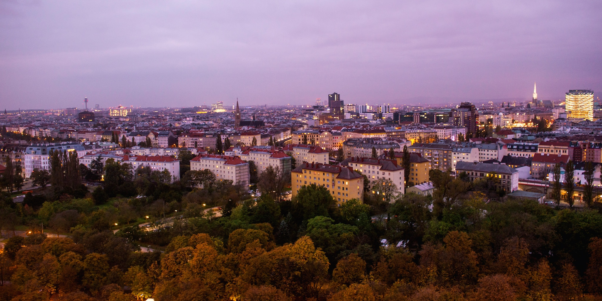 Both older and modern buildings stand out across the city of Vienna at dusk