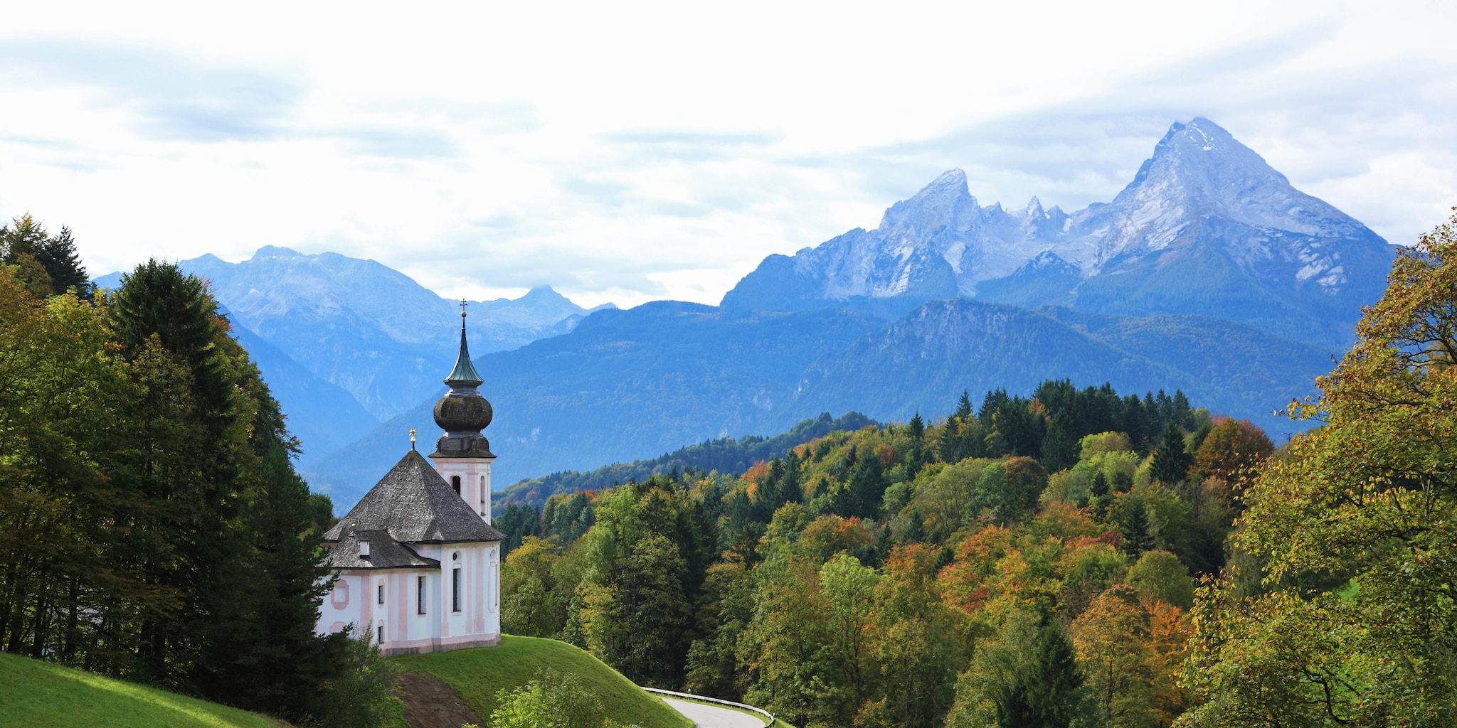 A little church with a steeple on a curvy road surrounded by mountains