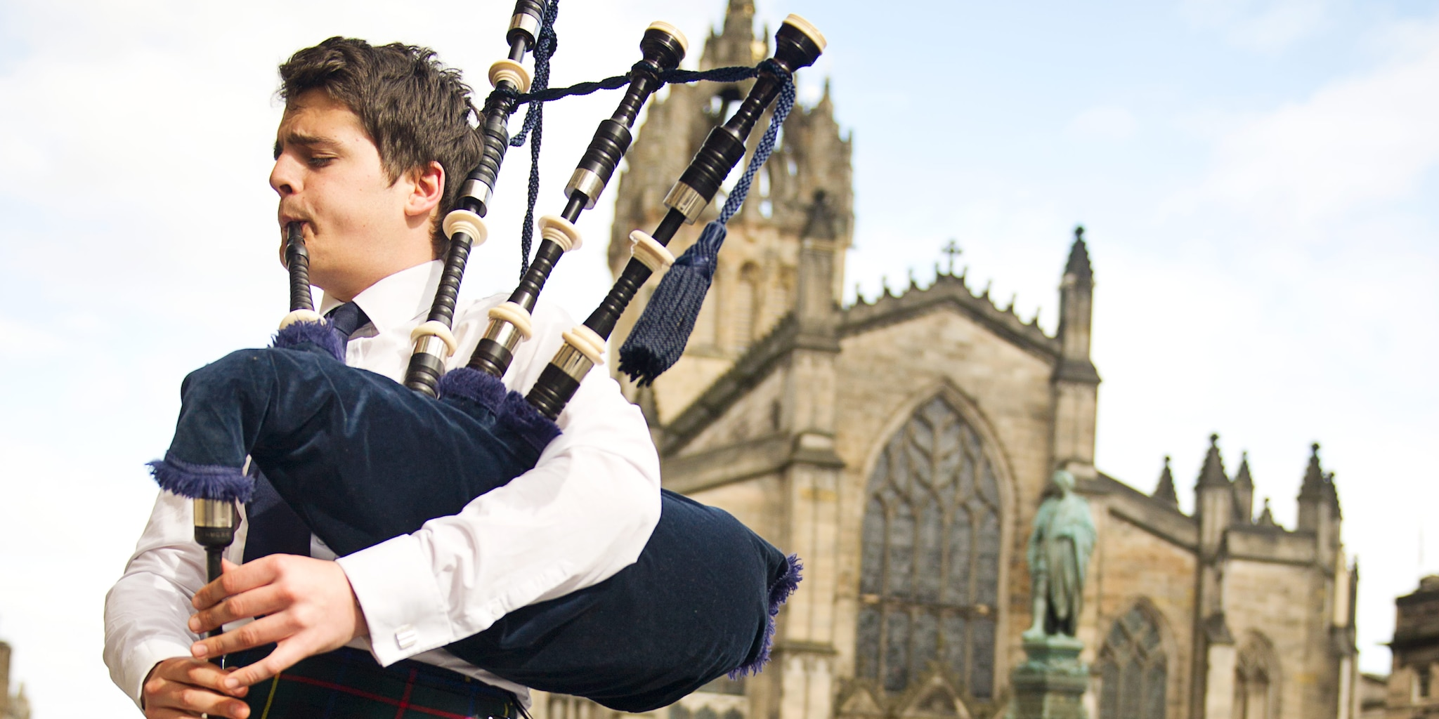 A bagpiper plays the bagpipes outside an old stone church