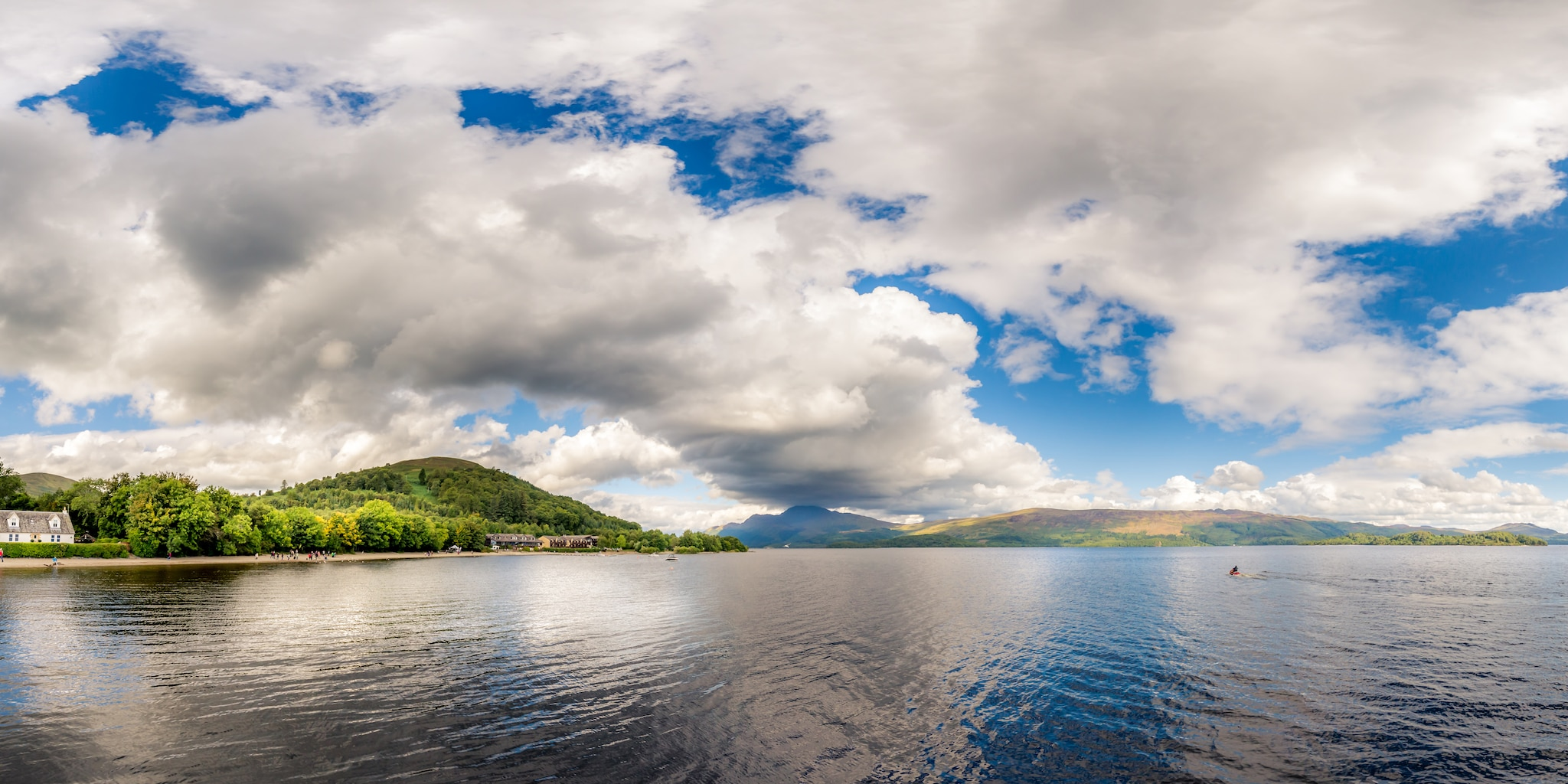 Cumulus clouds lie low over Loch Ness, surrounded by forested bluffs