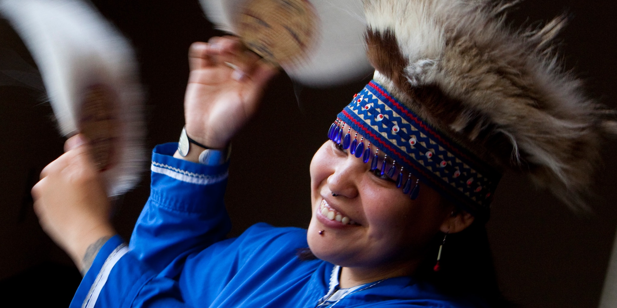 A dancing woman wears traditional Alaskan clothing and headdress