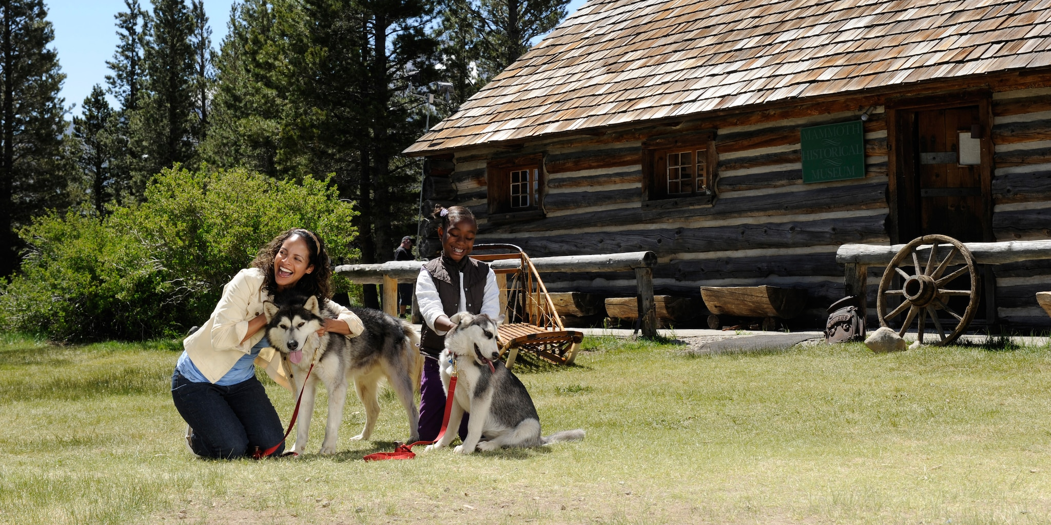 A mother and daughter pet two Siberian Huskies outside a log cabin