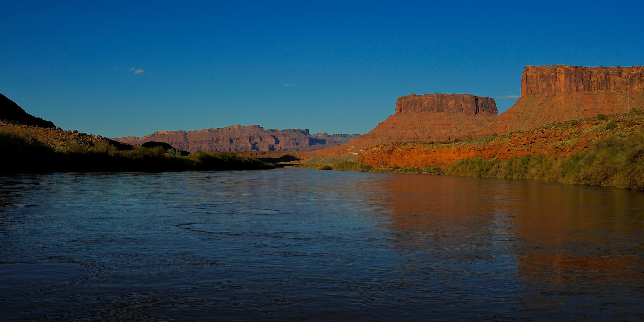 A tranquil area of the Colorado River surrounded by sandstone buttes
