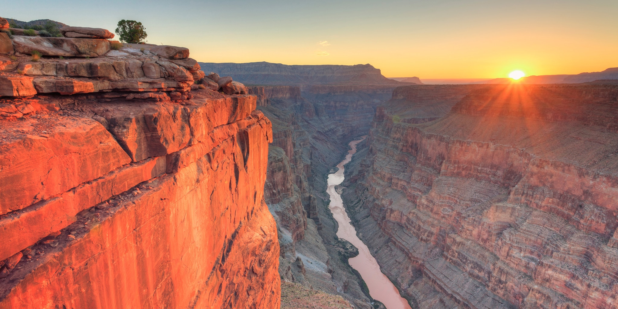 A river runs between canyon walls at sunset