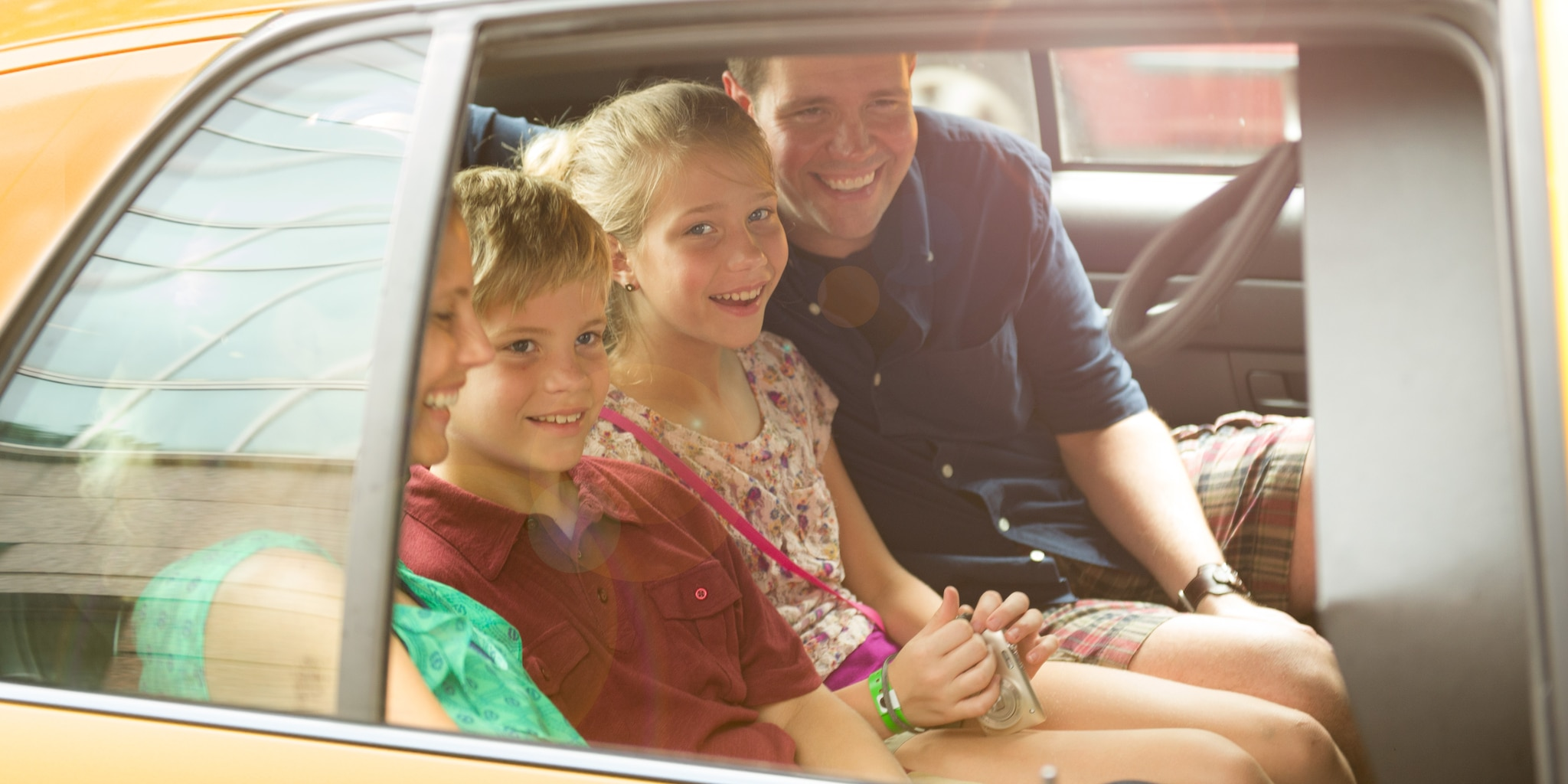 A smiling family of 4 rides in the back of a sedan