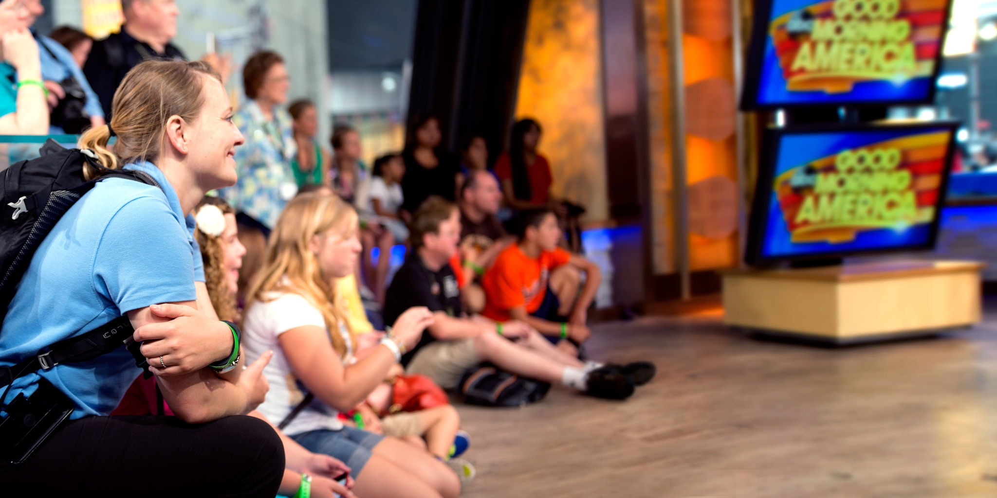 An audience sits on the floor in a television studio, watching the taping of 'Good Morning America'