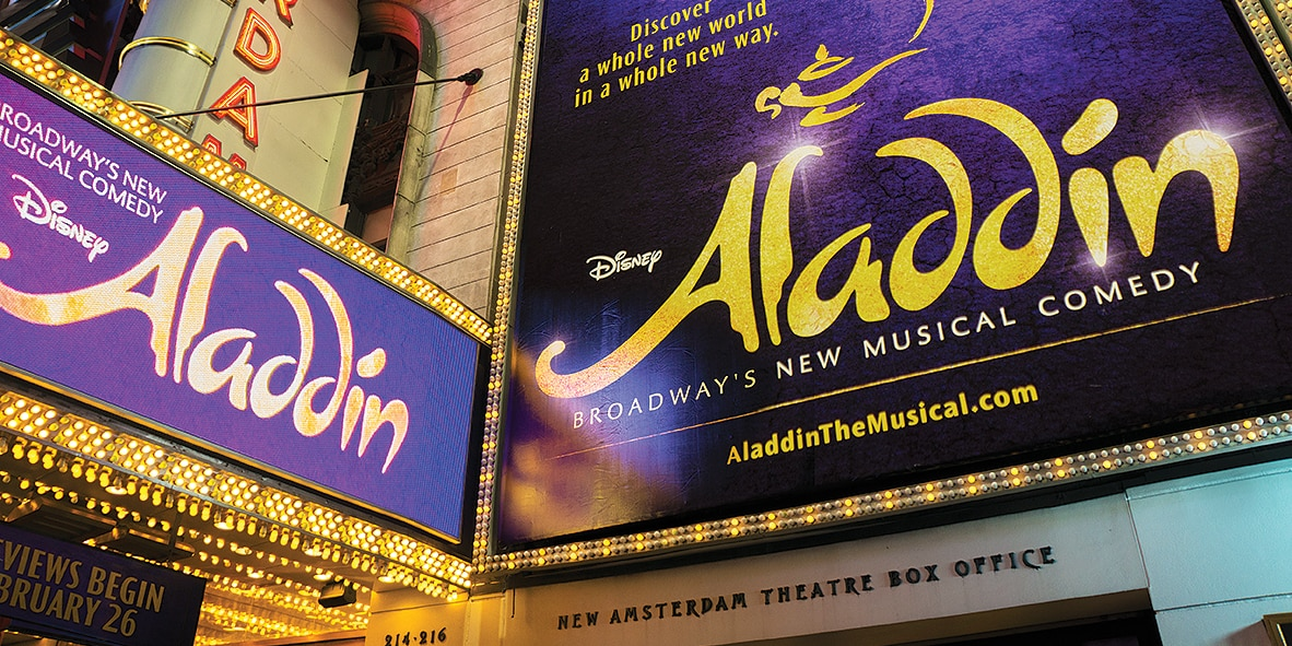 A marquee outside a Broadway theater that reads 'Aladdin'
