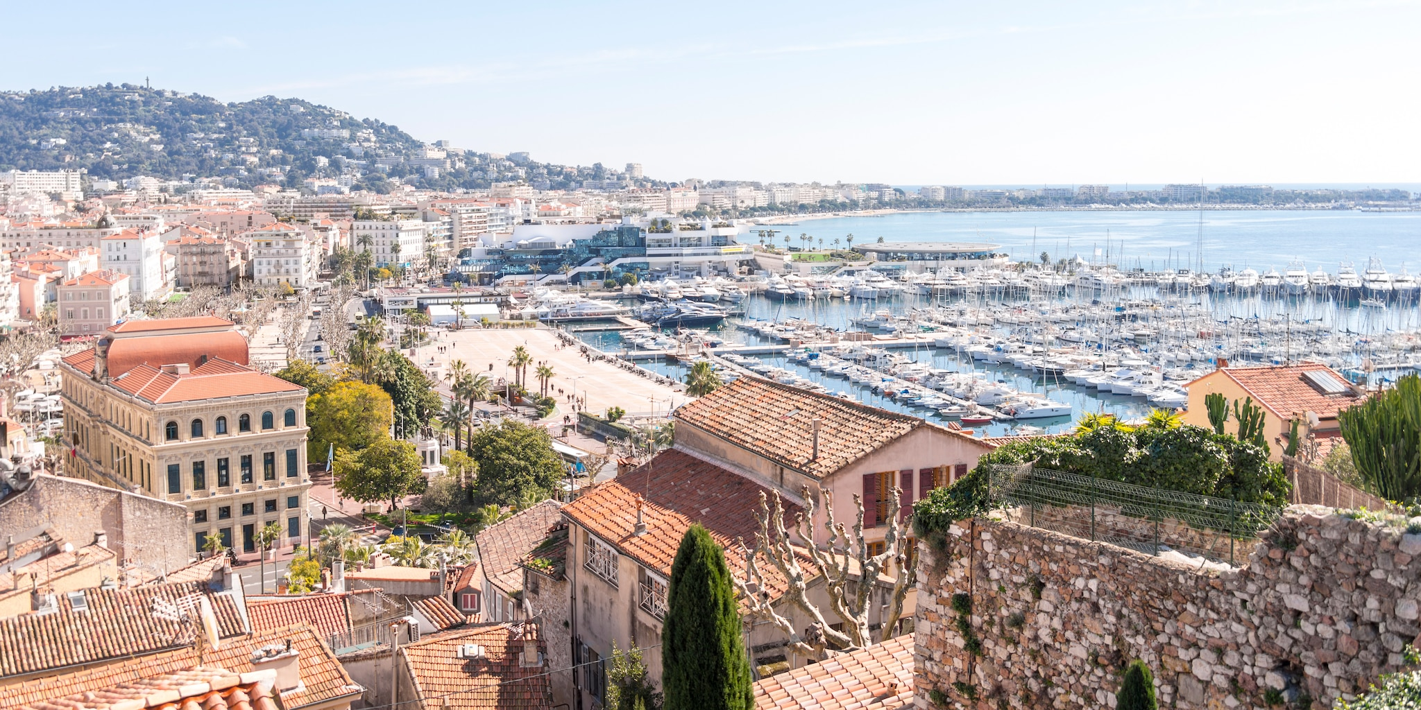 Boats docked in the Cannes Harbor, with multi storied, tile roof buildings hugging the shore