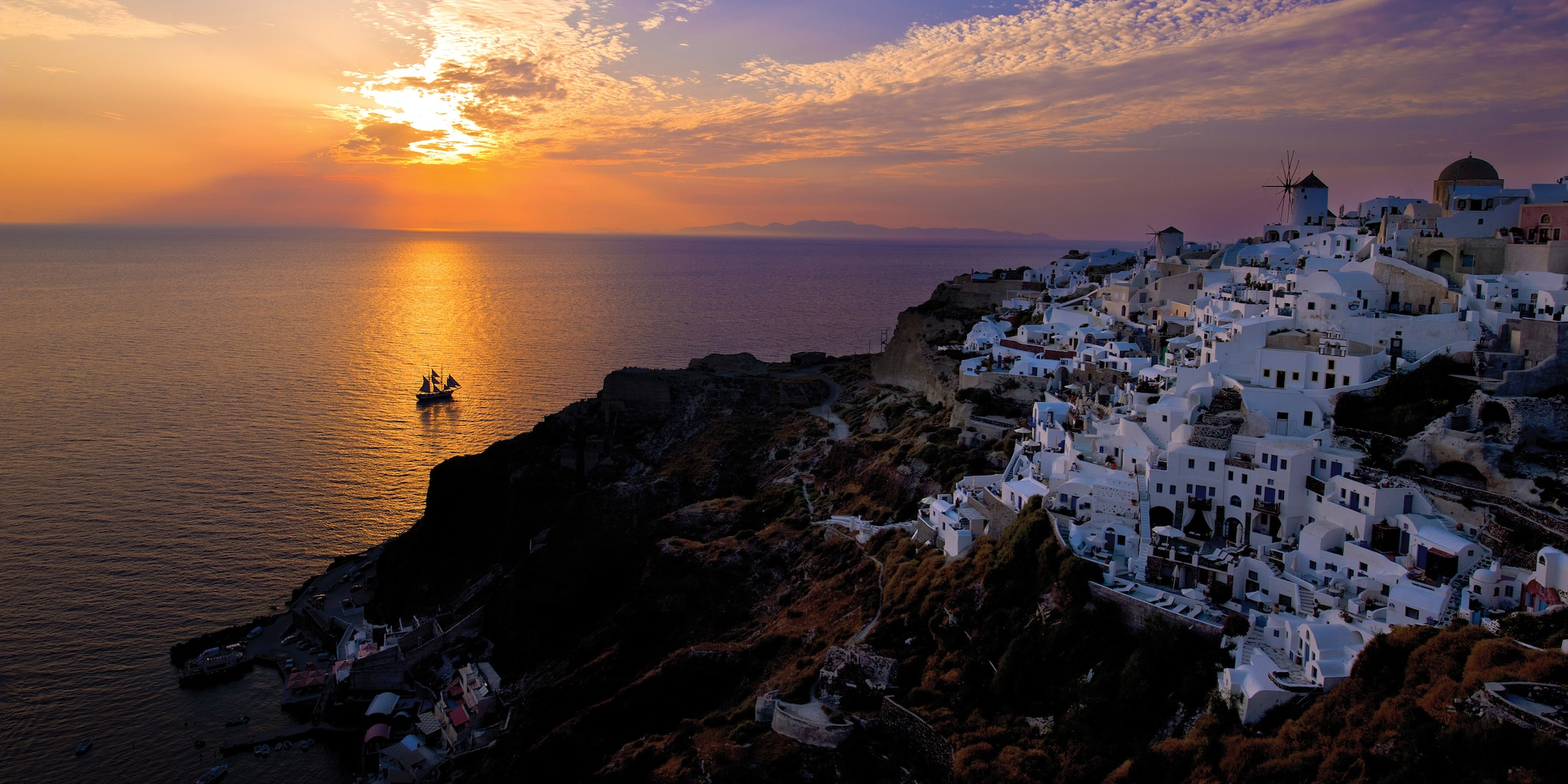 The sun sets over the Aegean Sea, with a small village of whitewashed houses on the nearby coast