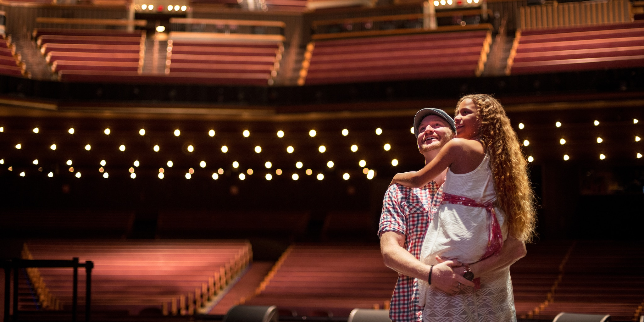 A father and daughter stand on stage at the Grand Ole Opry
