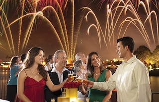 Two couples enjoy a champagne toast during a fireworks display