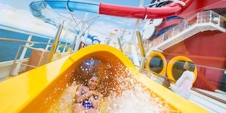 A girl glides down the AquaDuck water slide on the Disney Magic cruise ship