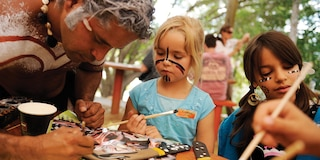 2 girls paint boomerangs with an Aboriginal artist