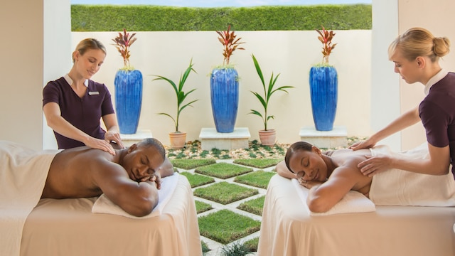 Man and woman enjoying separate massages together in a serene, indoor-outdoor spa